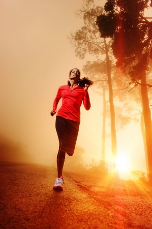 Athlete running on the road in morning sunrise training for marathon and fitness  Healthy active lifestyle latino woman exercising outdoors   photo