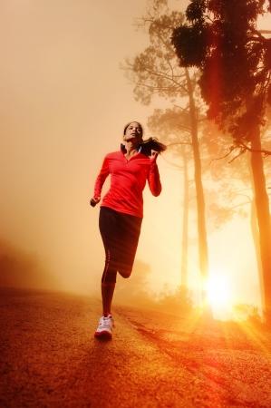 Atleet loopt op de weg in 's morgens zonsopgang training voor marathon en fitness gezonde, actieve levensstijl latino vrouw uitoefenen buiten