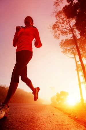 vitality: Athlete running on the road in morning sunrise training for marathon and fitness  Healthy active lifestyle latino woman exercising outdoors