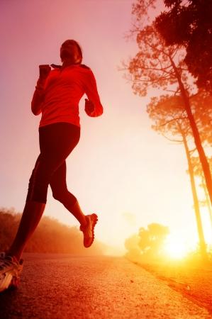 mujeres corriendo: Atleta corriendo por la carretera en la formaci�n de la ma�ana del amanecer de marat�n y de buena condici�n f�sica mujer de estilo de vida latino activo ejercicio al aire libre Foto de archivo