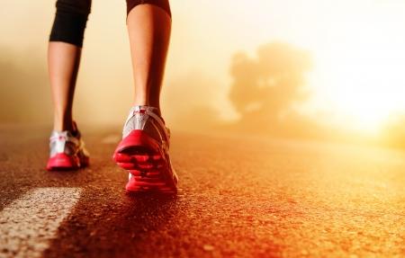 hacer footing: Pie de atleta corredor que se ejecutan en primer plano de carretera en la mujer zapatos de fitness concepto de la salida del sol jog bienestar de entrenamiento
