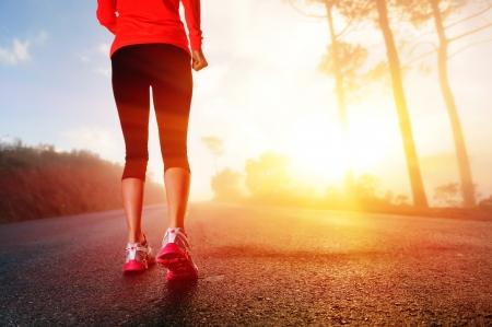 アスリート: アスリート ランナー足靴女性フィットネス日の出上の道路のクローズ アップで実行ジョギング ワークアウト ウェルネス コンセプト 写真素材