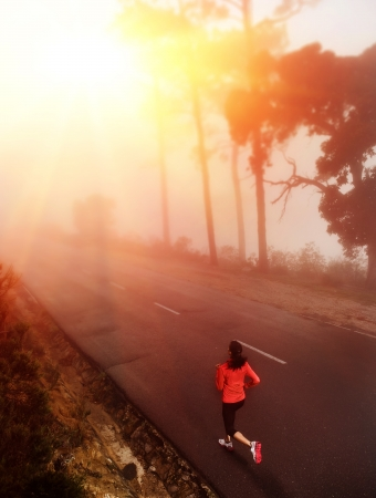 Healthy running runner woman early morning sunrise workout on misty mountain road workout jog  sunflare through the mist gives atmospheric feel and depth to this set of fitness images photo