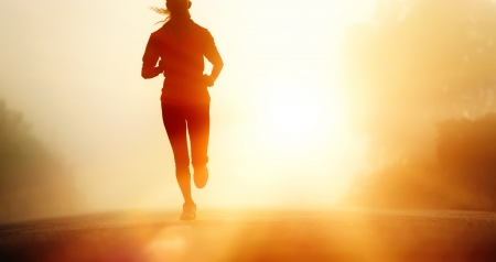 Runner athlete feet running on road  woman fitness silhouette sunrise jog workout wellness concept  photo