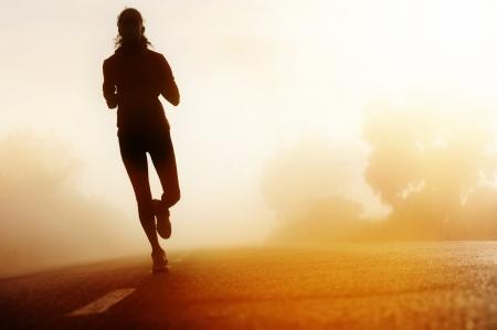 道路女性フィットネス シルエット日の出を実行しているランナー選手足ジョギング ワークアウト ウェルネス コンセプト 写真素材