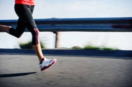 marathon running: Athlete runner motion blur running on road focus on shoe  woman speed sprint fitness training  Stock Photo