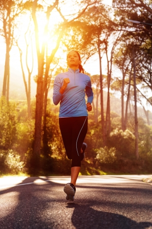 Runner athlete training running on road  woman fitness sun flare sunrise jog workout wellness concept  photo
