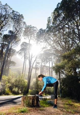 Athletic woman warming up before her morning workout in the forest mountain road  Runner training outdoors, healthy lifestyle concept