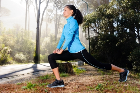 female athlete: Athletic woman warming up before her morning workout in the forest mountain road  Runner training outdoors, healthy lifestyle concept