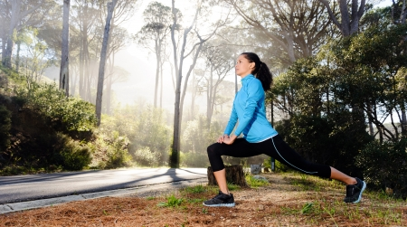 stretches: Athletic woman warming up before her morning workout in the forest mountain road  Runner training outdoors, healthy lifestyle concept