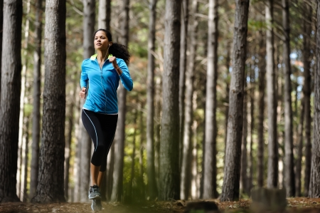 trail running: Woman running in wooded forest area, training and exercising for trail run marathon endurance  Fitness healthy lifestyle concept    Stock Photo