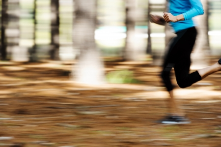 joggers: Action motion shot of runner training in forest with blur to show speed and sprinting   Stock Photo
