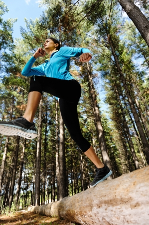 Woman trail running in the woods and jumping over logs while on extreme outdoor fitness training in forest   photo