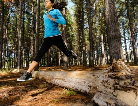 Woman trail running in the woods and jumping over logs while on extreme outdoor fitness training in forest