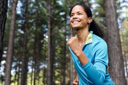 actief luisteren: Portret van een loper het luisteren naar muziek op de hoofdtelefoon tijdens het lopen buiten in een bos. gezonde wellness fitness levensstijl.