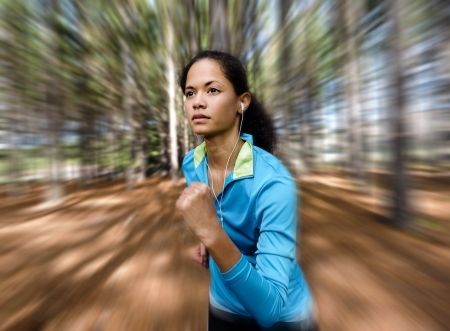Portrait of a runner listening to music on headphones while running outdoors in a forest. healthy wellness fitness lifestyle.  photo