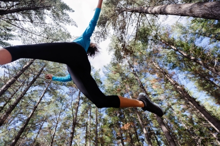 active lifestyle: low angle view of runner jumping and running in forest. healthy active lifestyle