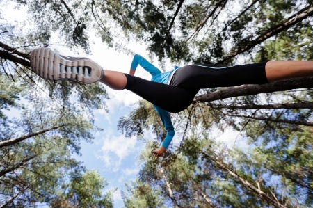 low angle views: low angle view of runner jumping and running in forest. healthy active lifestyle