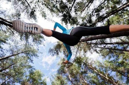 low angle views: �ngulo de visi�n baja de corredor de saltar y correr en el bosque. el estilo de vida activo y saludable