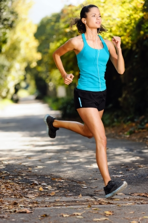 runner girl: running healthy fitness woman training for marathon outdoors in alleyway  vitality lifestyle exercise athlete  Stock Photo