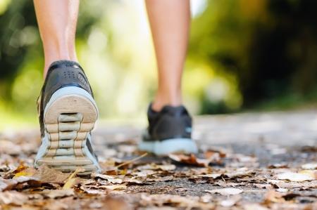 maraton: cerca de los pies de un corredor que se ejecuta en las hojas de oto�o de entrenamiento para la marat�n y estilo de vida de buena condici�n f�sica