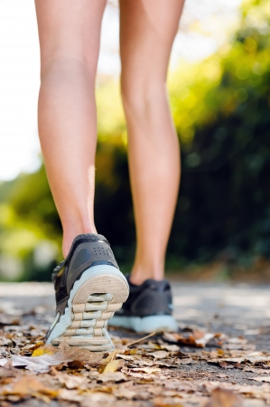 athletic activity: close up of feet of a runner running in autumn leaves training for marathon and fitness healthy lifestyle