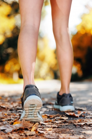 female legs: close up of feet of a runner running in autumn leaves training for marathon and fitness healthy lifestyle