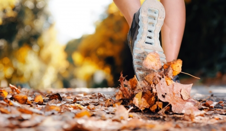marathon running: close up of feet of a runner running in autumn leaves training for marathon and fitness healthy lifestyle