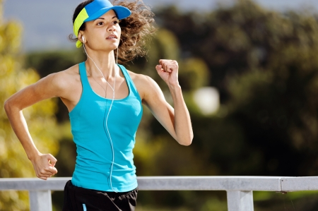 Portrait of a woman athlete runner training outdoors with cap and headphones listening to music  endurance sport   Stock Photo