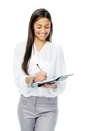 Friendly confident businesswoman writing in her organizer isolated on white background. photo