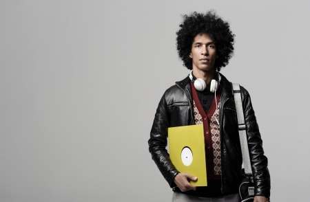 Retro dj portrait in fashion style isolated on grey brackground in studio. Modern music man with afro hairstyle, headphones and vinyl record. photo