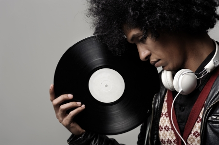 Retro dj portrait in fashion style isolated on grey brackground in studio. Modern music man with afro hairstyle, headphones and vinyl record. Stock Photo - 14342380