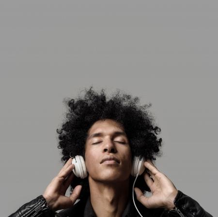 Retro man met afro luisteren naar muziek op DJ hoofdtelefoon met gesloten ogen. geïsoleerd op grijze achtergrond in de studio. Stockfoto