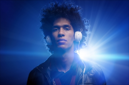 Confident dj portrait with club lights lens flare and retro man with afro and headphones photo