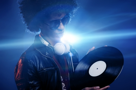Dj with vinyl record in club wearing sunglasses listening to party music and lens flare photo