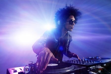 musica electronica: Club DJ con afro peinado de reproducción de música de mezcla en el plato giratorio de vinilo en la fiesta con gafas de sol con la llamarada de la lente de las luces de la vida nocturna. Foto de archivo