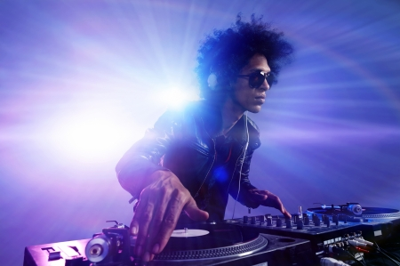 electronic music: Club DJ with afro hairstyle playing mixing music on vinyl turntable at party wearing sunglasses with lens flare from nightlife lights.