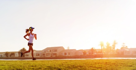 runner girl: Athlete running at sunset panorama with copyspace