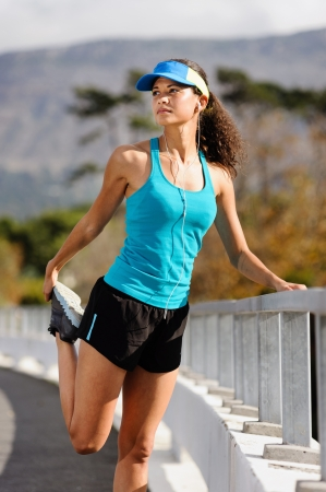 outdoor fitness: woman runner stretching leg muscle before running outdoors for athlete training.