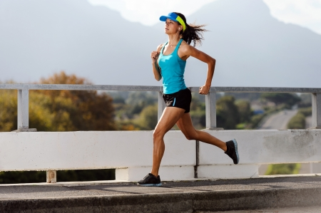 female runner: Athlete running on bridge. action shot of runner in mid air. healthy lifestyle fitness woman Stock Photo