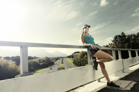 portrait of an athlete resting after running workout outdoors on a bridge. healthy fitness woman photo