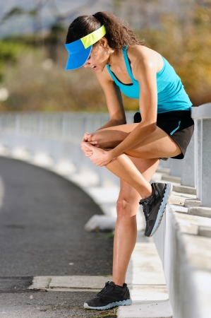 knee injury for athlete runner. woman in pain after hurting her leg while training for fitness marathon photo