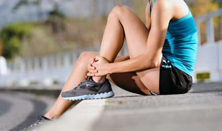 runner girl: runner with ankle injury holds foot to reduce pain. running problem for athlete training outdoors