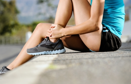 ankle: runner with ankle injury holds foot to reduce pain. running problem for athlete training outdoors