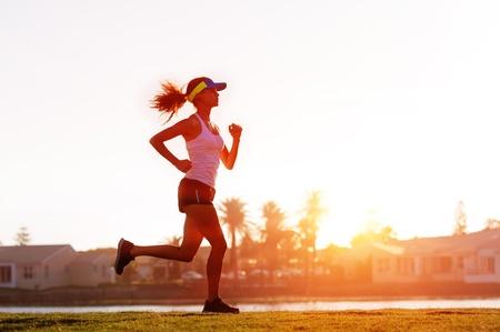 girl jogging: silhouette of a woman athlete running at sunset or sunrise. fitness training of marathon runner. Stock Photo