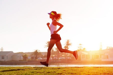 female athlete: silhouette of a woman athlete running at sunset or sunrise. fitness training of marathon runner. Stock Photo