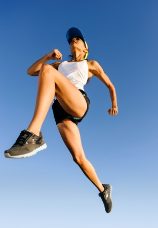 marathon running: Athlete jumping shot from low angle with sky background Stock Photo