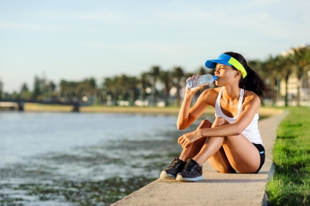 thirsty runner drinking water and sitting on the edge of a lake.  photo