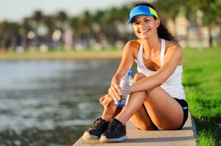 Portrait of a woman athlete runner resting after a long workout outdoors in the park. healthy happy fitness lifestyle.  photo