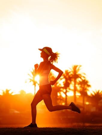 silhouette of a woman athlete running at sunset or sunrise. fitness training of marathon runner. Stock Photo